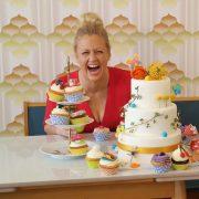 Barbara Schöneberger lachend vor einer Torte und Cupcakes